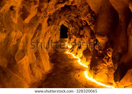 Underground cave with artificial lights down - stock photo