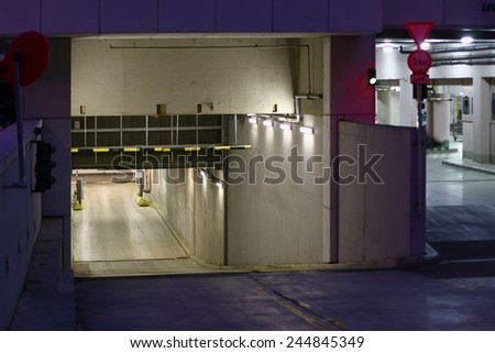 underground garage entrance with lights inside at night - stock photo