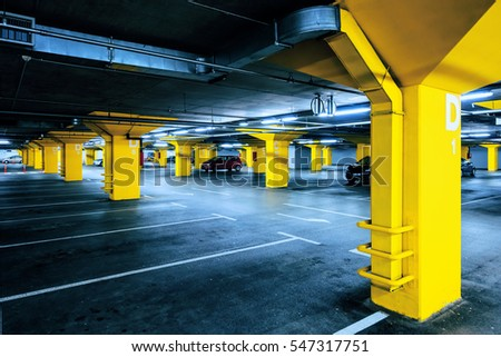 Underground garage parking lot with few cars and empty spaces for more vehicles, urban exploration and geometry in architecture
