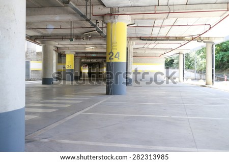 Underground park of a mall with columns and ventilation ducts - stock photo