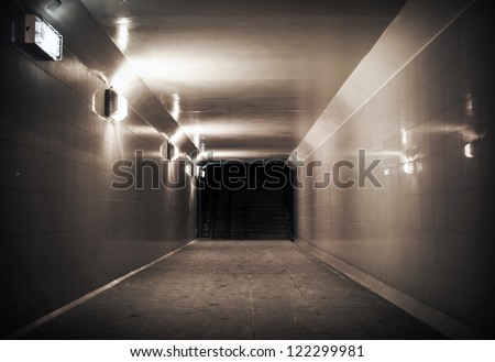 Underground passage with lights and stairs in dark end - stock photo