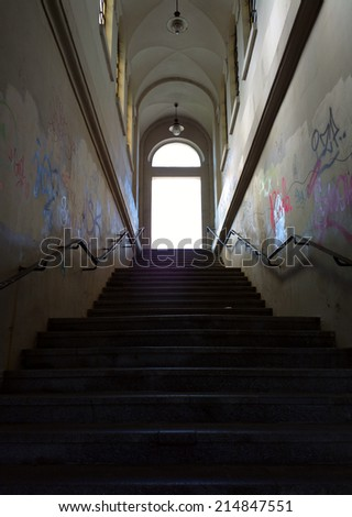 Underground passage with stairs in the glowing end. - stock photo