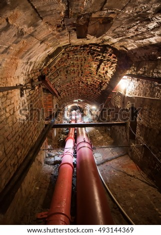 Underground pipeline tunnel with lighting, arched brick walls and ceiling