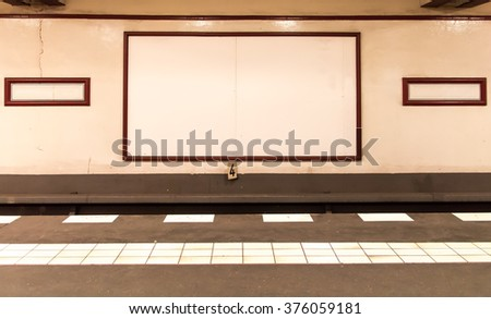 underground platform with empty advertising boards on the wall