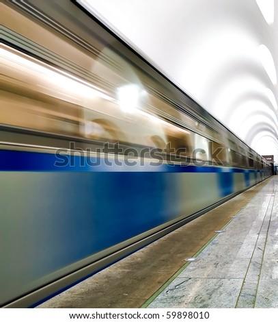 underground platform with moving train - stock photo