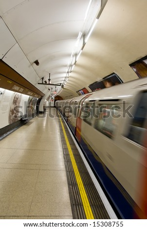 Underground train arriving at Charing Cross station in London. Motion blur. - stock photo