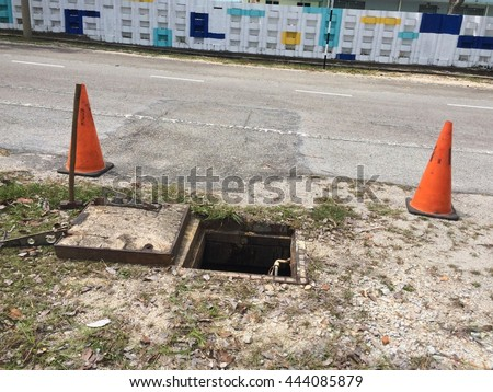 Underground work. Open manhole and two orange cone  without and air supply hose