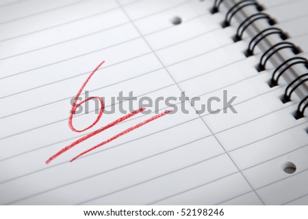 underlined mark six written in red letters on a spiral pad, shallow DOF