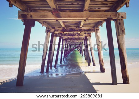 Underneath the pylons of a long jetty pier on sunny beach overlooking the sea, with applied retro vintage style filters. Taken at Grange, South Australia.  - stock photo