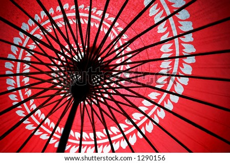 Underneath the red Japanese umbrella with spiral flower - stock photo