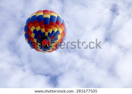 Underneath view of a single hot air balloon rising up to a blue sky full of clouds