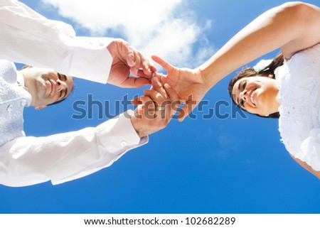 underneath view of groom putting wedding on bride - stock photo