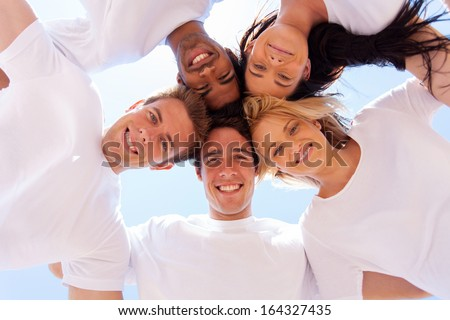 underneath view of group of friends in a circle looking down - stock photo