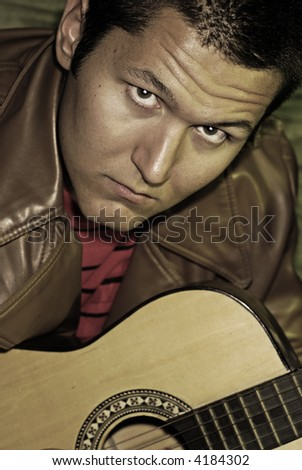 Undersaturated portrait of a young guy with a guitar - stock photo