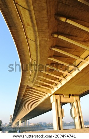 Underside of a winding yellow modern bridge, on a late sunny afternoon. - stock photo