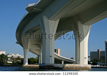 underside of curved concrete bridge support against blue sky - stock photo