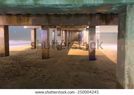 Underside of pier at night in Coney Island Brooklyn, long time exposure - stock photo