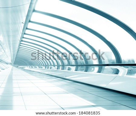 Underside wide angled and perspective view to steel blue glass airport ceiling through high rise building skyscrapers, business concept of successful industrial hallway and passageway architecture