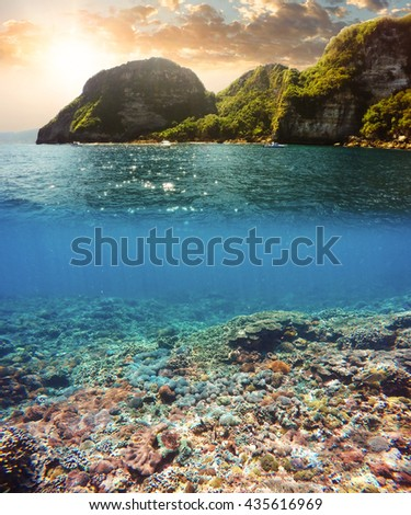 Underwater and surface split view in the tropics paradise with boat, fish and coral reef, above waterline, beautiful view on tropical island. Nusa Penida bali, Indonesia. Holiday vacation concept