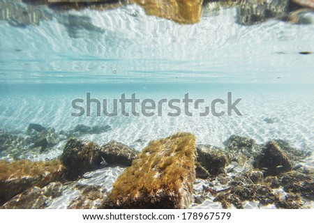 Underwater backdrop with white sand and rocks - stock photo