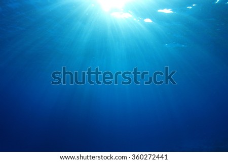 Underwater blue ocean background photo with sun and sunbeams - stock photo
