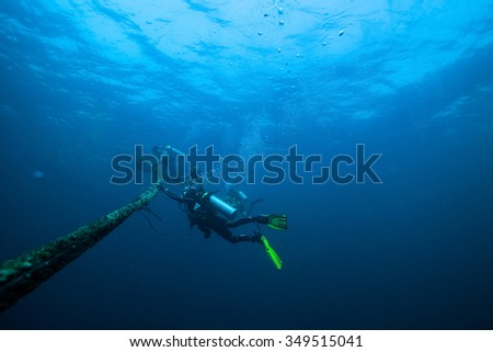 Underwater Blue Sea and diver doing safety stop  - stock photo