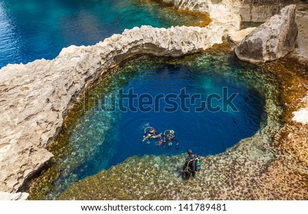 underwater cave in the form of heart and divers at Azure Window in Gozo, Malta - stock photo