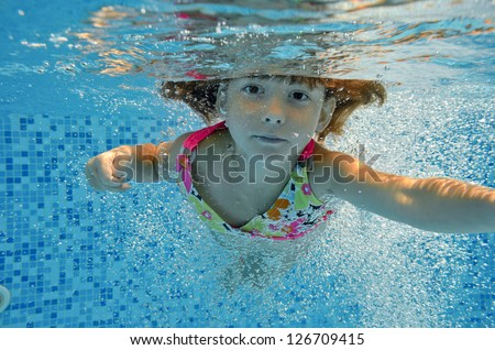 Underwater child jumps to swimming pool, beautiful little girl swims and having fun. Kids sport on family summer vacation. Active holiday