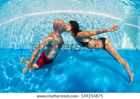 Underwater couple kissing in swimming pool. - stock photo