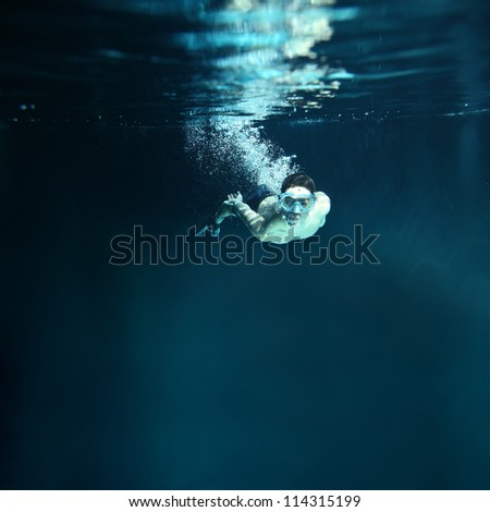 underwater diver isolated on blue background - stock photo