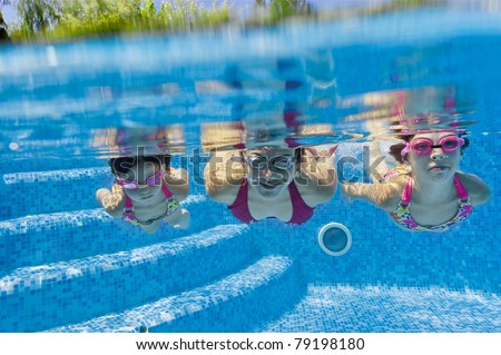 Underwater family in swimming pool - stock photo