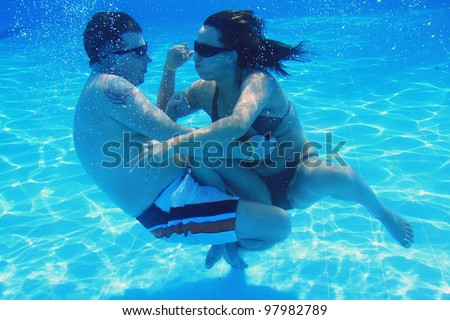 Underwater fun of couple in the swimming pool - stock photo