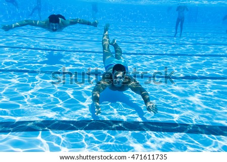 Underwater fun. Two young handsome men swimming underwater and diving in the swimming poll. Sport and leisure.