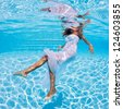 Underwater girl fashion portrait with white dress in swimming pool. - stock photo