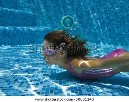 Underwater girl in swimming pool - stock photo