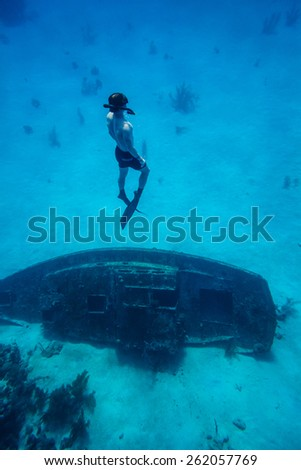 Underwater image of a Freediver resurfacing after visiting a shipwreck - stock photo