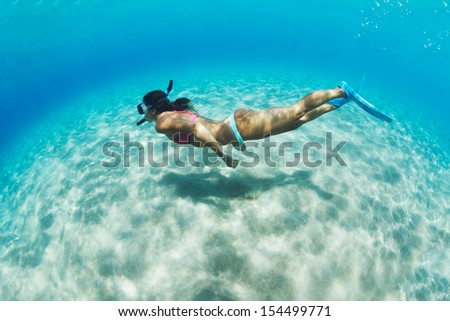 Underwater image of a woman snorkeling in tropical sea over sandy bottom - stock photo