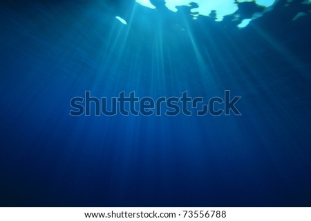 Underwater image of sun rays in the blue sea - stock photo