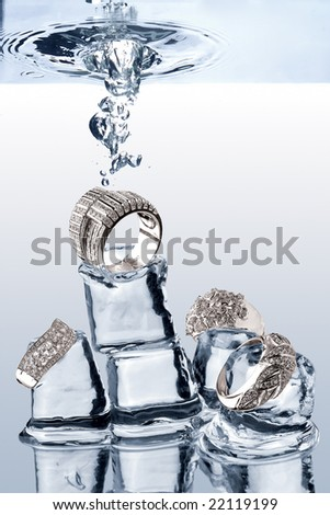 Underwater Jewelery. A view of jewelery being dropped on ice cubes underwater. - stock photo