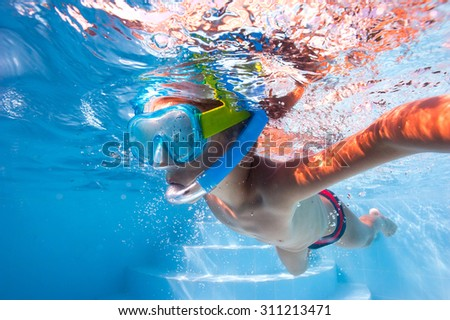 Underwater kid in swimming pool with mask. - stock photo