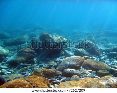 Underwater light on a rocky seafloor in the Mediterranean sea - stock photo