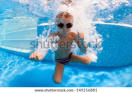 Underwater little kid in swimming pool with goggles. - stock photo