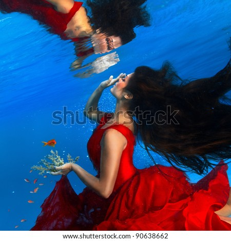 underwater photo beautiful brunette wearing red dress looking on her mirror at water surface - stock photo