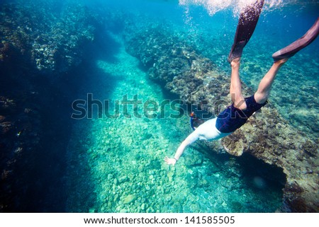 Underwater photo of a young man diving - stock photo