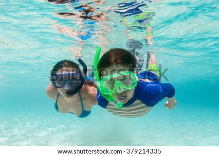 Underwater photo of mother and son family snorkeling in turquoise ocean water - stock photo