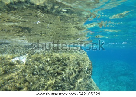 Underwater photo of rocky cliff in Mylopotas beach, Ios island, Cyclades, Greece