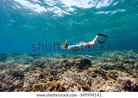 Underwater photo of woman snorkeling and free diving in a clear tropical water at coral reef - stock photo