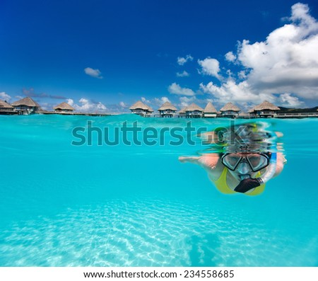Underwater photo of woman snorkeling in clear tropical waters in front of overwater villas - stock photo