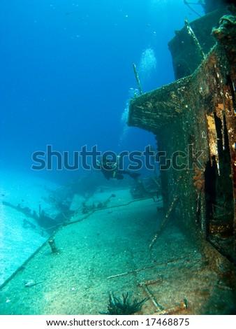 Underwater Photographer Shooting a Sunken Ship in Cayman Brac - stock photo