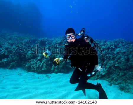 Underwater Photographer surrounded by a Hawaiian Reef in Maui - stock photo